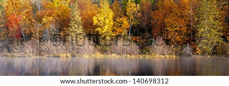 Michigamme Morning Autumn color along the Michigamme River in Michigan's Upper Peninsula. - stock photo