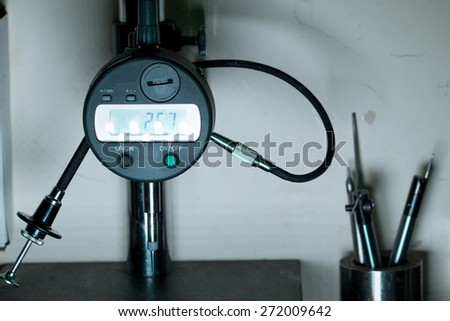 Micrometer caliper indicator at measuring stand in quality assurance department labaratory - stock photo