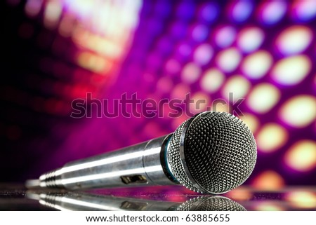microphone against purple disco background - stock photo