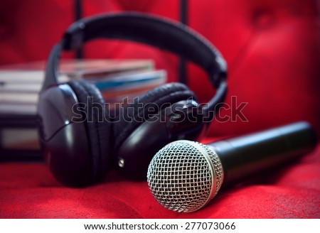 microphone and head phone on red sofa leather use for entertainment and karaoke theme - stock photo