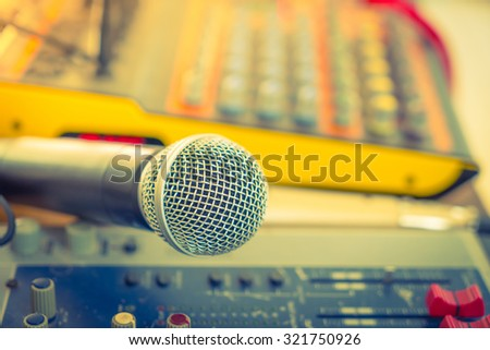 Microphone and Music mixer desk with various knobs ( Filtered image processed vintage effect. ) ( Filtered image processed vintage effect. ) - stock photo