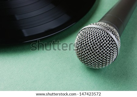 microphone and old vinyl record  on a green background