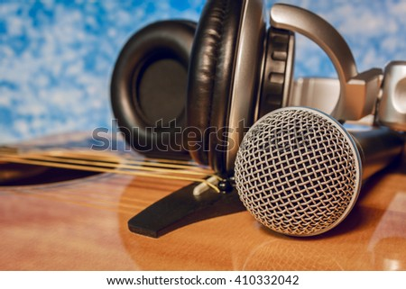 microphone,headphone on classic guitar  background in home recording studio. - stock photo