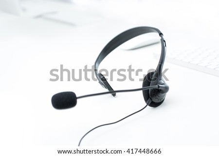 Microphone headset on white table with blur computer keyboard background - operator, call center,customer service and telemarketing concepts - stock photo