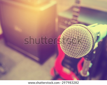 Microphone in a recording studio or concert hall with amplifier in out of focus background. : Vintage style and filtered process. - stock photo