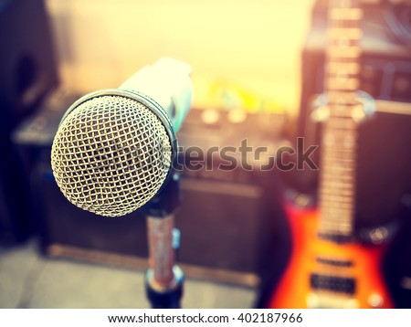 Microphone in a recording studio or concert hall with electric guitar in out of focus background. : Vintage style and filtered process. - stock photo