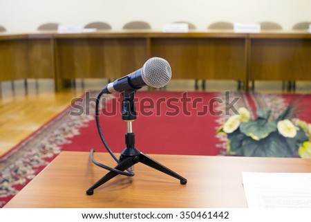 Microphone in an empty auditorium on background  red carpet. - stock photo