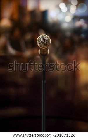microphone in concert hall or conference room on a dark background