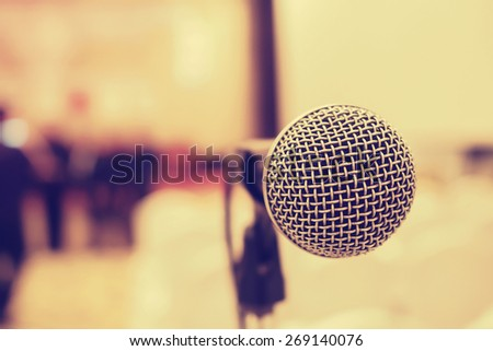 Microphone in concert hall or conference room with de-focused bokeh lights in background. : Vintage style and  filtered process - stock photo
