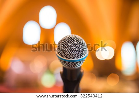 Microphone in concert hall or conference room with defocused bokeh lights in background - stock photo