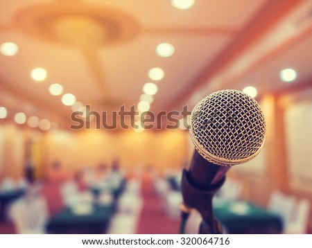 Microphone in concert hall or conference room with defocused bokeh lights in background. Extremely shallow dof. Vintage style and filtered process. - stock photo