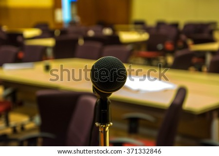 Microphone in concert hall or conference room. yellow tone