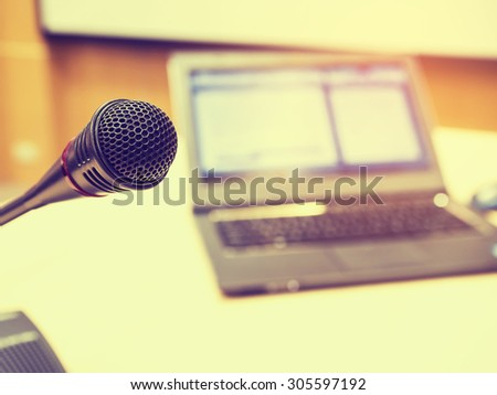 Microphone in conference room or symposium event with de focused laptop is working in background.  Vintage style and filtered process - stock photo
