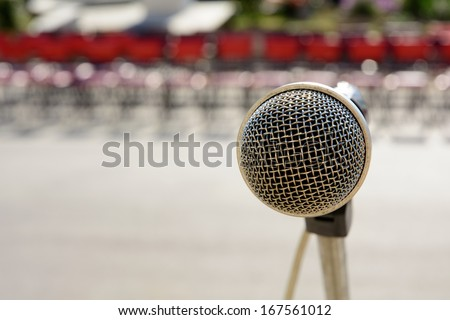 Microphone in front of red chairs - stock photo