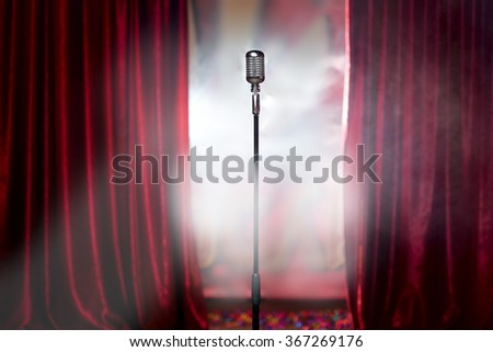 microphone in front of red curtain on an empty stage after the concert, smoke - stock photo