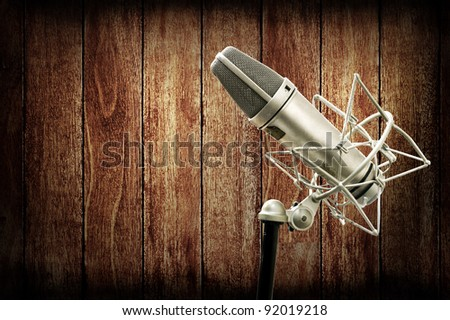 Microphone in studio with wooden wall, Music studio concept - stock photo