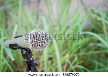 microphone on a stand with blurred green plant, copyspace - stock photo