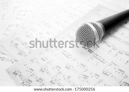 microphone on music sheet - stock photo