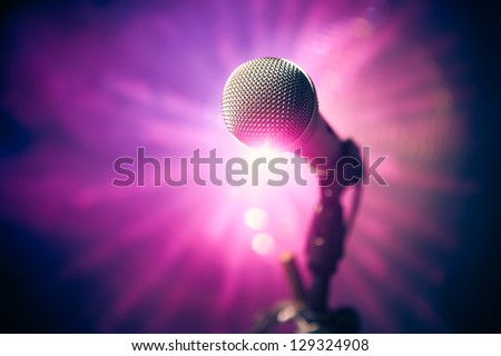 microphone on stage against purple rays