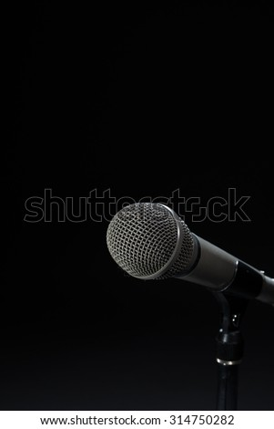 Microphone on stand against seamless black background.