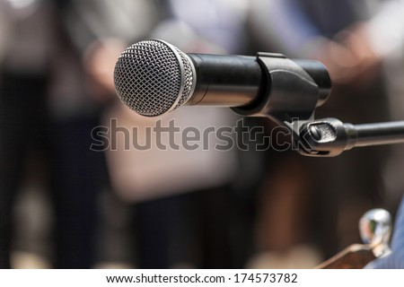 Microphone on the background blurred figures of people during a rally closeup - stock photo