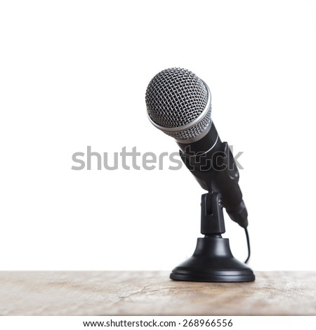 Microphone on wooden table, on white background. - stock photo