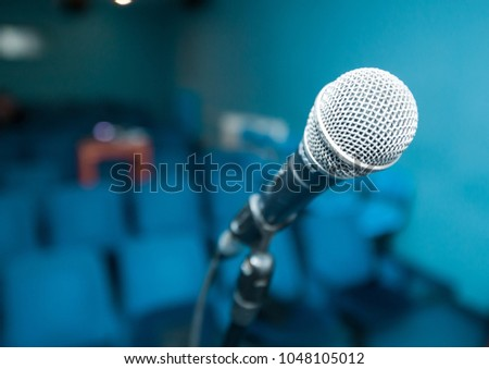 Microphone over blurred empty meeting room