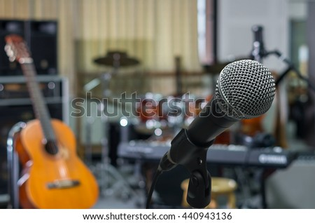 Microphone over the Abstract blurred photo of music band instrument background, musical concept