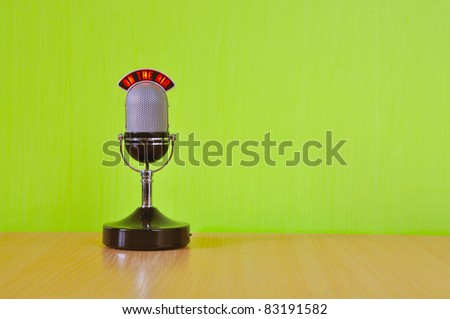 microphone stands on the table, the green wall