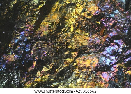 Microscope image of colorful copper ore. This is copper sulphide called Chalcopyrite, It has the chemical formula (CuFeS2). - stock photo