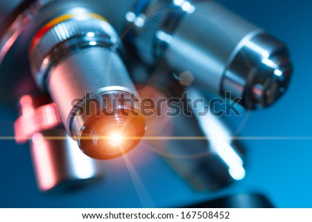 microscope lens with a beam of green light - stock photo
