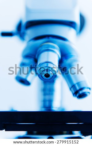 Microscope objective lens in modern laboratory interior. Blue cast light represent purity and clinical mood. Useful file for your hospital brochure, medical article and other purpose. - stock photo