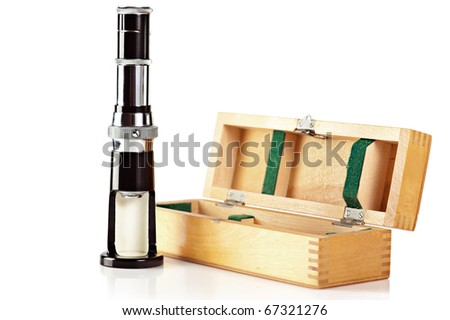 Microscope. Old fashioned mini microscope and wooden box isolated on white - stock photo