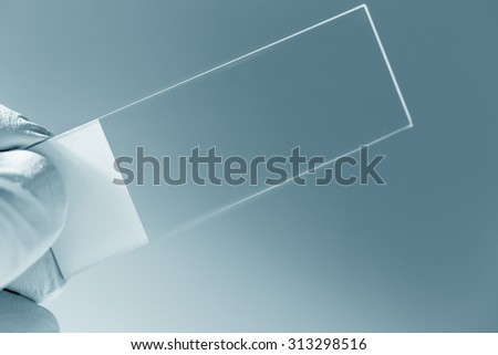 microscope slide in hand - stock photo