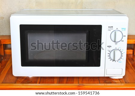 Microwave oven on the table in kitchen - stock photo
