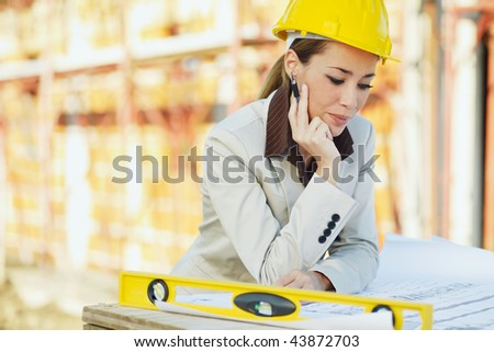 mid adult architect examining blueprints and smiling. Copy space - stock photo
