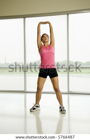 Mid adult Asian woman standing with arms raised above head stretching.
