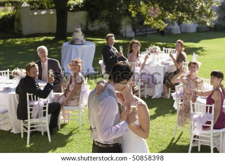 Mid adult bride and groom in garden among wedding guests, holding wineglasses, kissing - stock photo