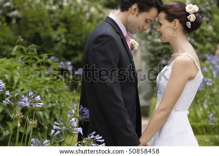 Mid adult bride and groom in garden, face to face, side view - stock photo