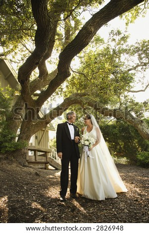 Mid-adult bride and groom standing outside of church. - stock photo