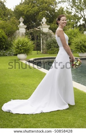 Mid adult bride at poolside, holding bouquet, side view