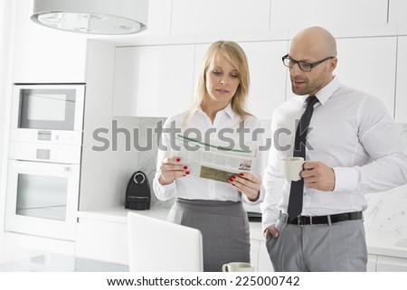 Mid adult business couple reading newspaper while having coffee in kitchen - stock photo