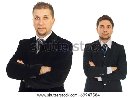Mid adult business man in front of camera standing with hands crossed and his young colleague in background - stock photo