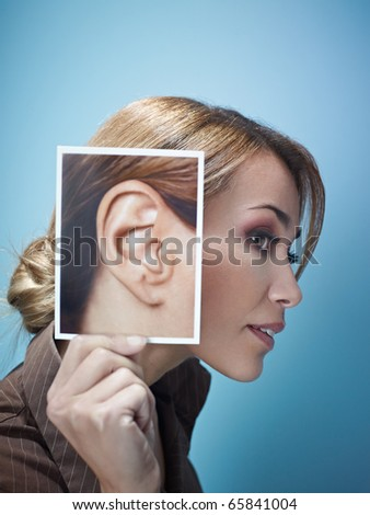 mid adult business woman holding photo of her ear on blue background. Vertical shape, side view, head and shoulders, copy space - stock photo