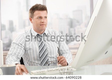 Mid-adult businessman at work, sitting in office using computer.? - stock photo