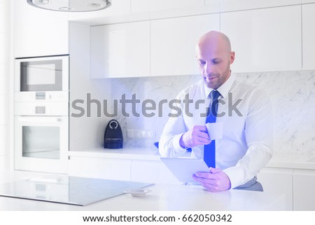 Mid adult businessman having coffee while using tablet PC at kitchen counter