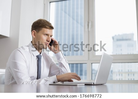 Mid adult businessman on call while using laptop at home