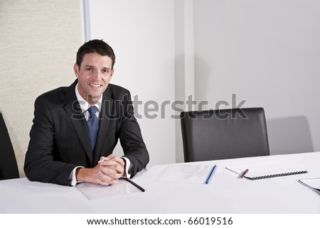 Mid-adult businessman, 30s, smiling with confidence at camera, sitting on boardroom next to empty chair - stock photo