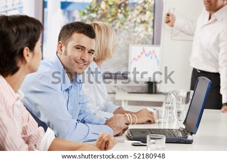 Mid-adult businessman sitting on business meeting with colleagues in office, looking at camera, smiling.