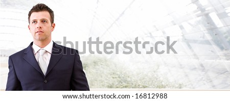 Mid adult businessman standing in front of windows inside officebuilding, looking away. Business banner. - stock photo